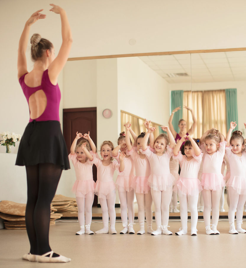Young girls in a ballet class with adult instructor cropped